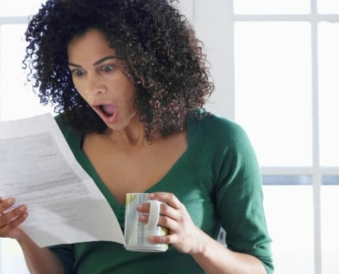 woman looking shocked at unexpected expenses (bill in hand)