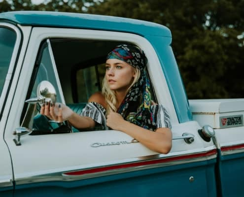 bohemian woman in blue and white truck, looking at herself in side view mirror