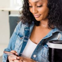 young woman in jean jacket smiling holding cell phone learning how to increase savings fast