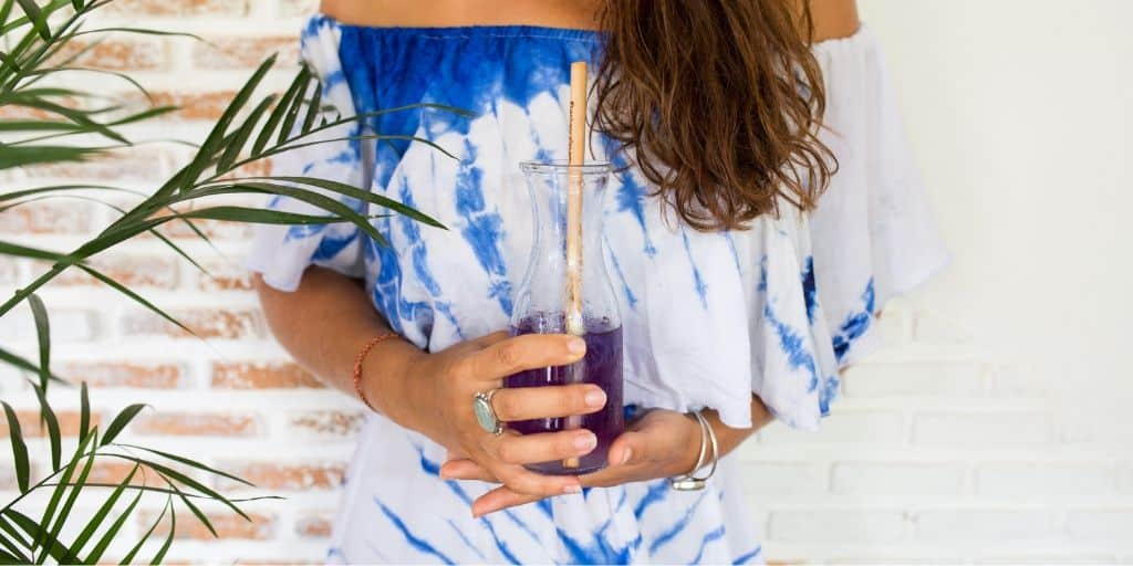 Young, abundant woman with purple juice in hands next to plant