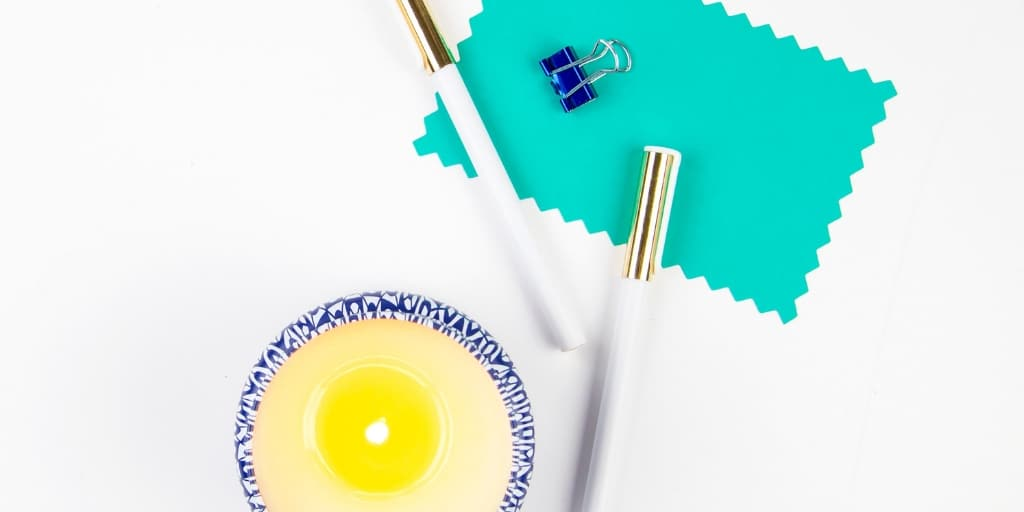 white desktop with pen and candle