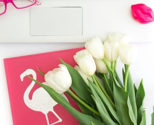 white desktop with white tulips, hot pink glasses and hot pink paper