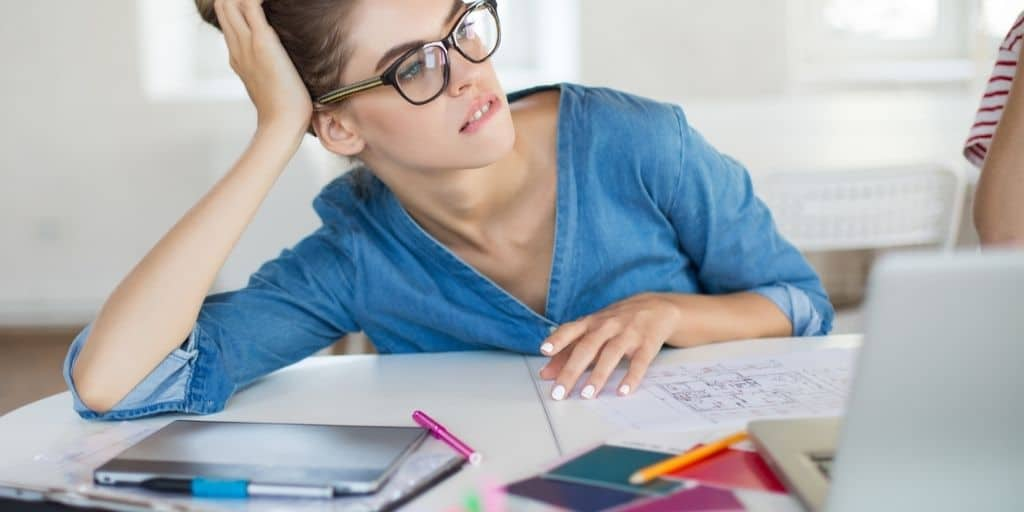 woman with glasses at desk, looking worried and wondering how to stop spending money on unnecessary things