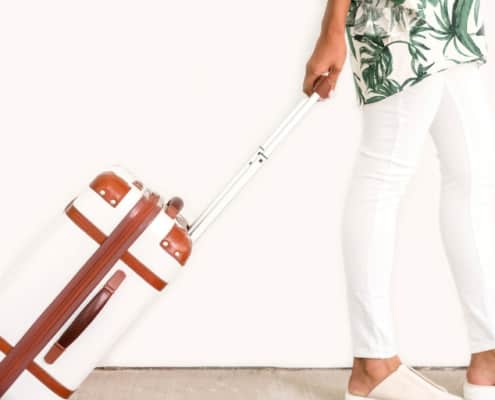 woman in traveling clothes with white pants and white luggage