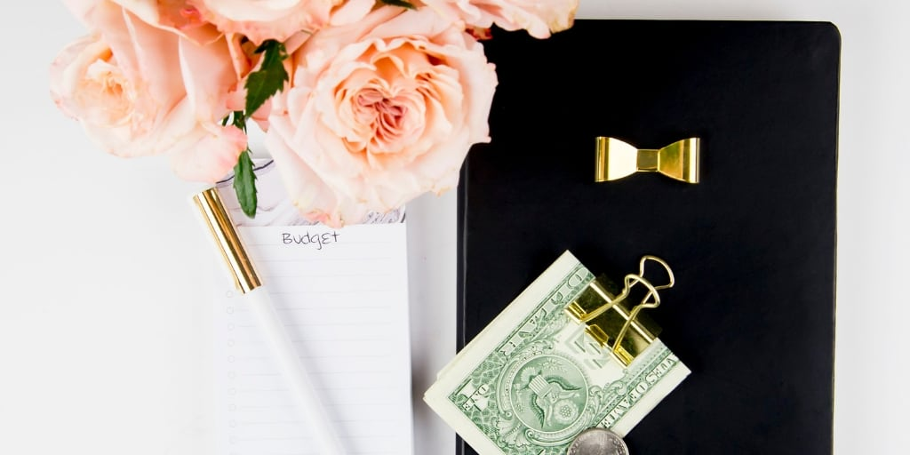 desktop with pink flowers, money in a clip, notepad and pen