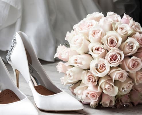 gorgeous white satin wedding heels and light pink rose bouquet