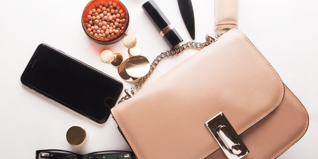 purse and makeup on white desktop