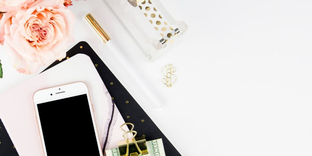 white desktop with flowers, money in clip and phone