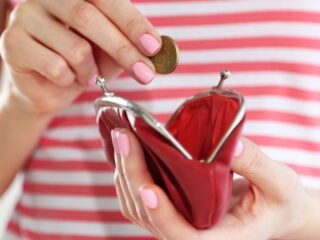 woman in red striped shirt putting coins into red coin purse because of frugal living tips with big impact