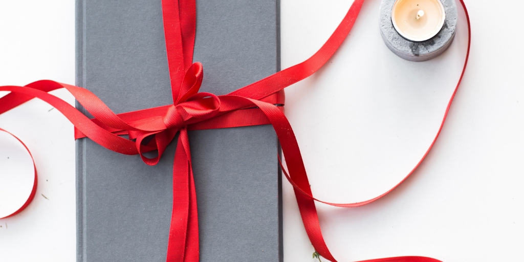homemade holiday gift wrapped in a grey box with a red ribbon on a desk