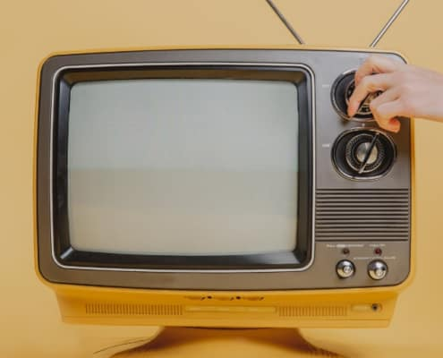 vintage television on yellow background, someone turning it on