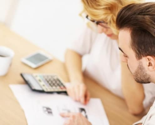 couple looking at finances with calculator on desk, figuring out how to drastically cut household expenses
