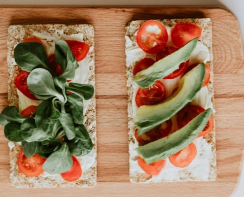 two flatbreads with spinach, tomato, and ricotta toppings on wooden cutting board