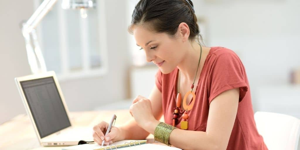 young woman at desk smiling, figuring out how to spend less money and save more