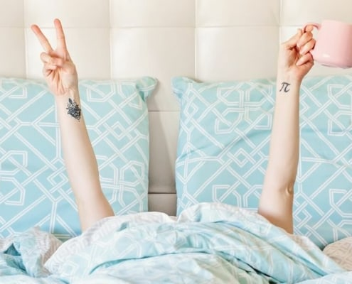 unemployed woman in bed with coffee and doing a peace sign, thinking about surviving unemployment