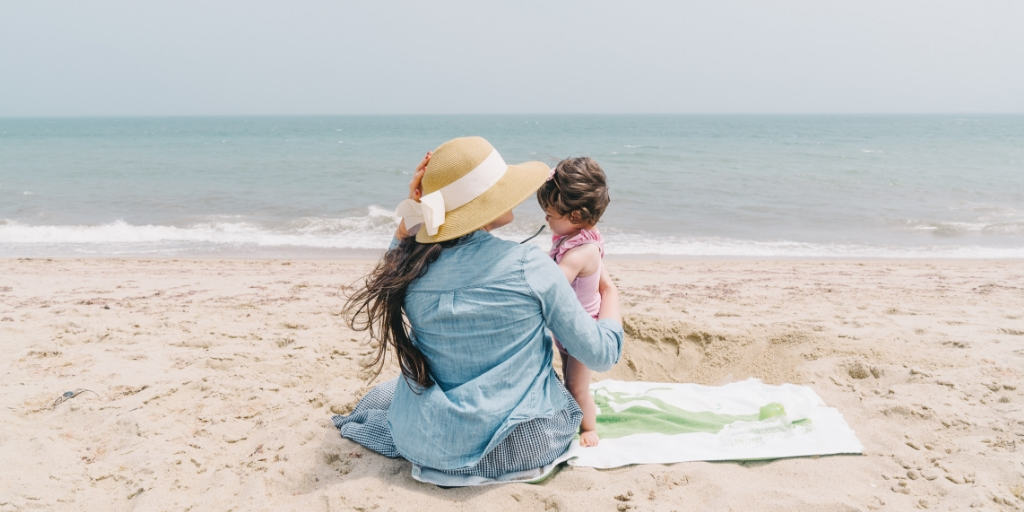 mother with child on beach, thinking about time vs money
