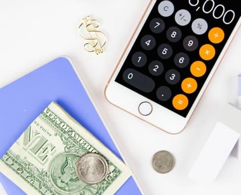 white desktop with calculator, money, blue notepad