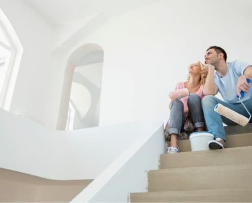young couple sitting on stairs of new home, feeling house poor