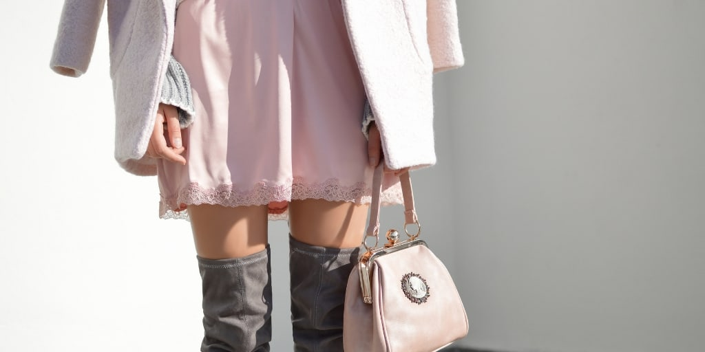 woman in designer boots and purse, wondering how to stop spending money on unnecessary things
