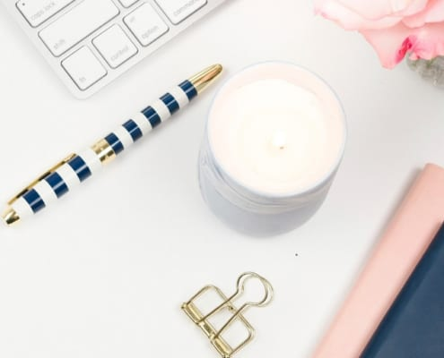 desktop with keyboard, pink flowers, a candle, a pen