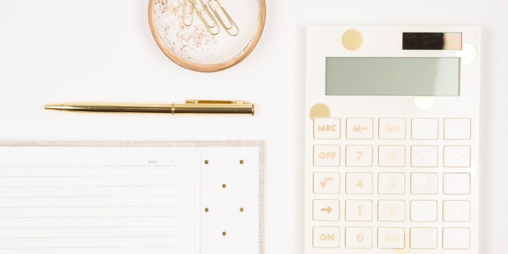 white desktop with white calculator, pen, notepad