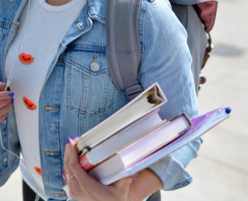 student holding textbooks and walking to class
