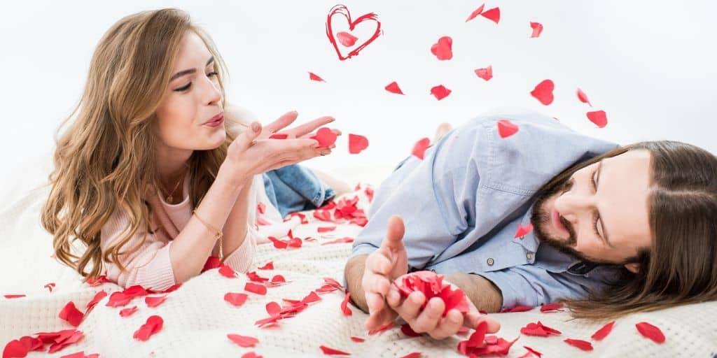 couple playing with rose petals as part of cheap valentine's day gift ideas