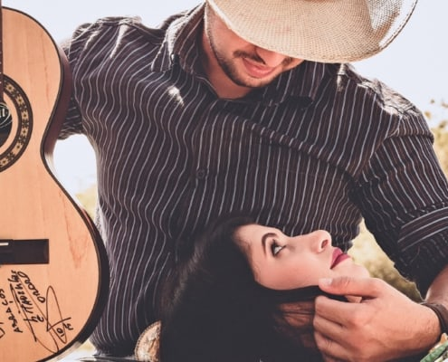 man in cowboy hat holding a guitar with woman's head in his lap