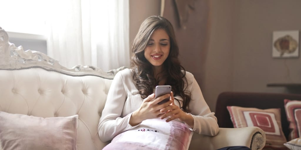 young woman sitting on pink chaise, texting her long distance boyfriend