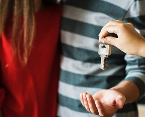 realtor handing keys to couple for their first home