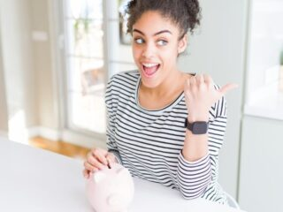 young woman with piggy bank, pointing and looking and smiling about importance of saving money for the future