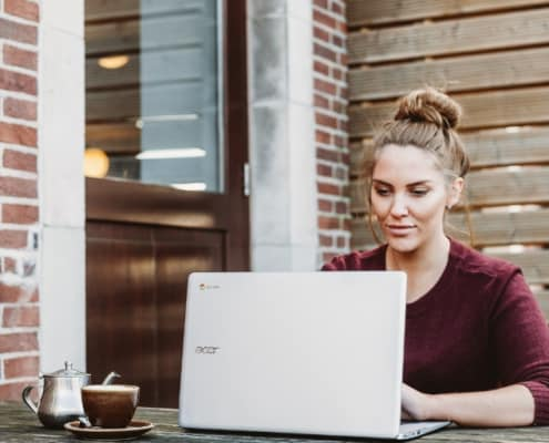 woman sitting outdoors at computer with brick wall background