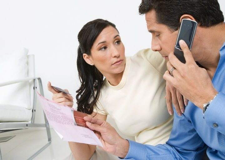 wife and husband dealing with zombie debt collector on phone