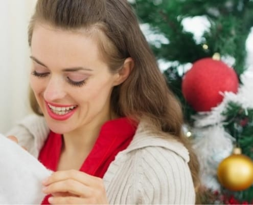 young woman looking into her stocking on Christmas