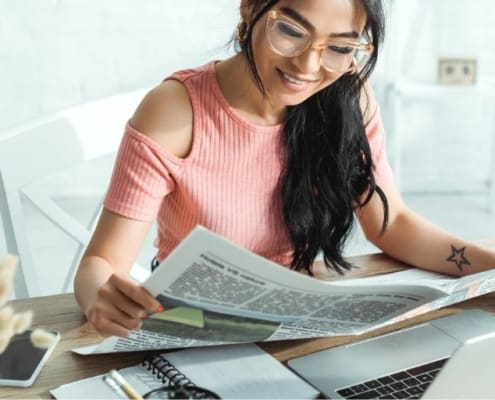woman with glasses, reading newspaper about to get investment decision questions answered