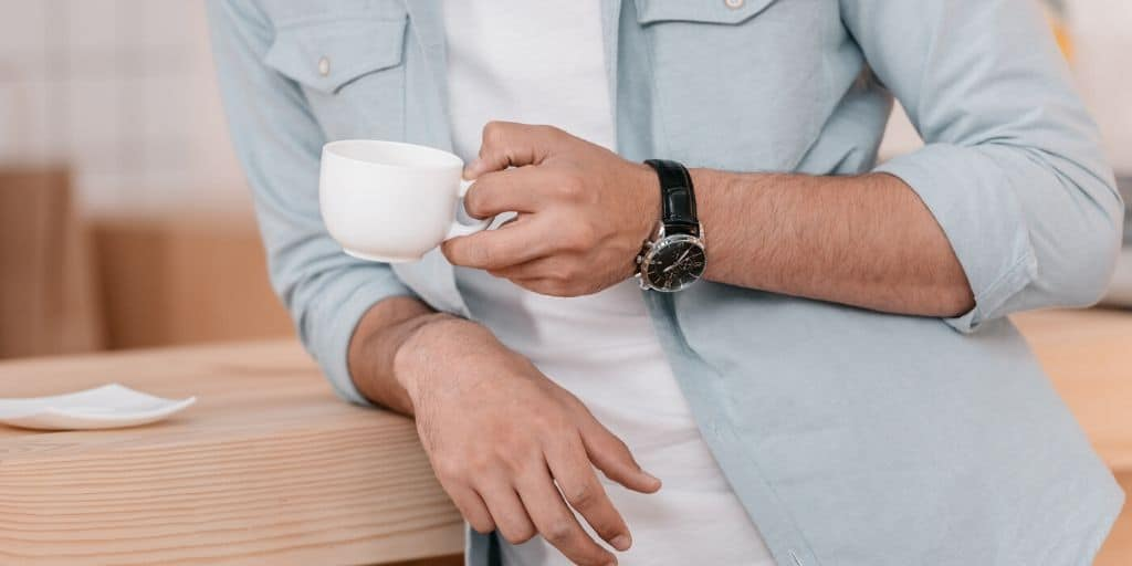 man who has everything leaning on counter with coffee and watch gift
