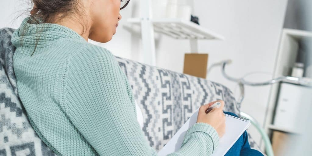 young woman in apartment, making notes on how to negotiate rent