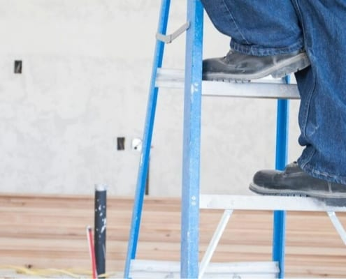 contractor on ladder, working on major home repair costs