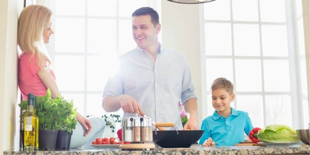 family in kitchen, all cooking together a meal to eat at home instead of eating out