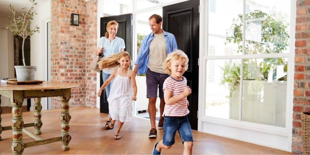 family of four running into their new home, going through the homeowner's insurance shopping process