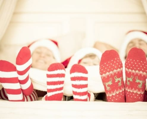 family laying down in bed, with Christmas socks on