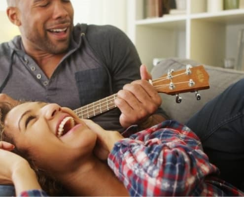 couple on couch, man playing ukele as part of list of cute couple things to do