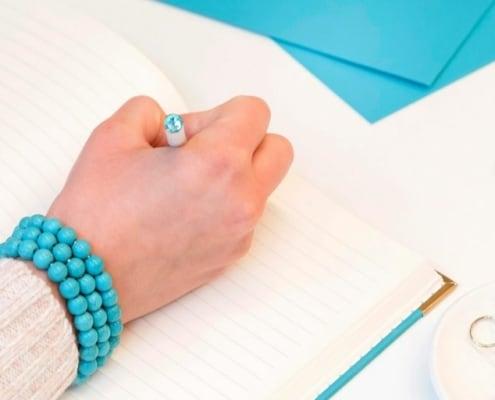 womans' hand using (bujo) bullet journal savings trackers