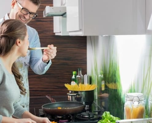 couple cooking together, working on correcting money imbalance in relationship