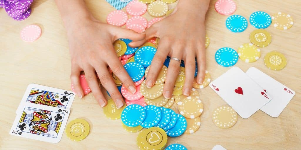 table flatlay with poker chips and cards, fun money saving games