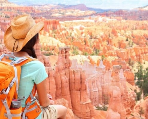 woman with backpack overlooking canyon as fun thing to save up for