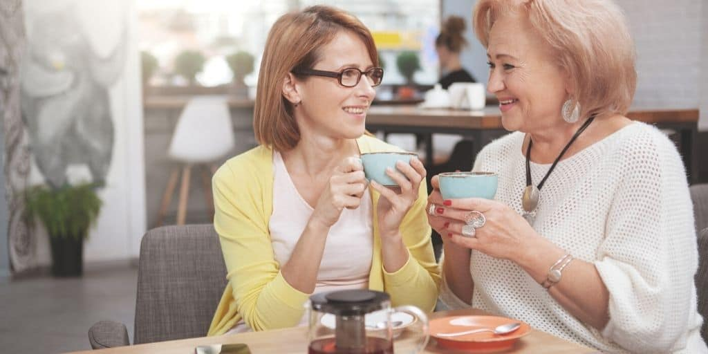 adult woman drinking tea with mom at restaurant for mother's day