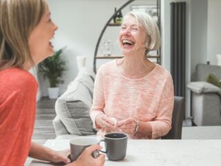 adult daughter and mother laughing together over tea