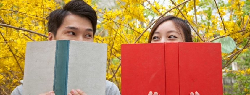 couple sitting on park bench behind books, flirting with each other - park date ideas