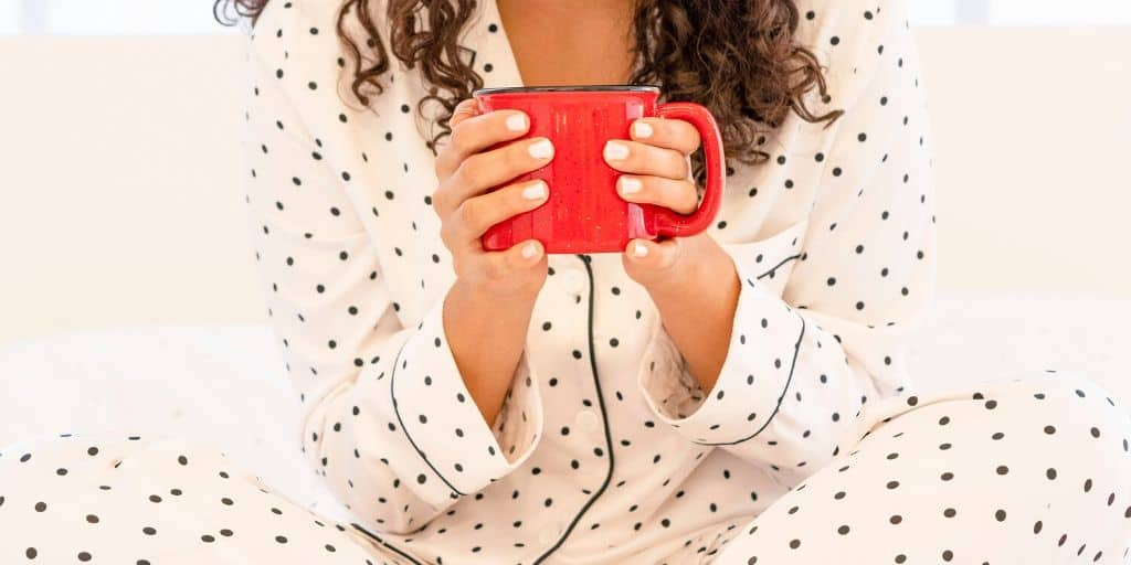woman smiling, holding mug of hot cocoa for what to do when you're bored without friends